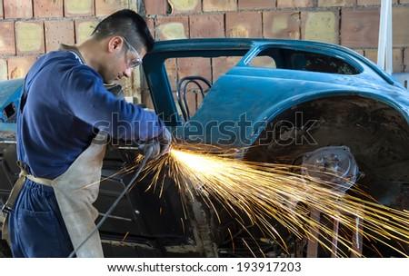 Man working on car body - stock photo