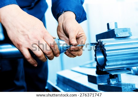 Man working on drilling and boring machine in workshop. Industry, industrial concept. - stock photo