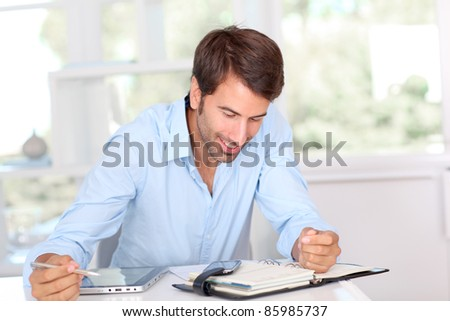 Man working on electronic tablet in office - stock photo