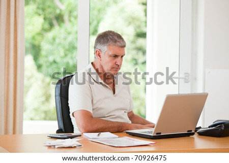 Man working on his laptop at home - stock photo