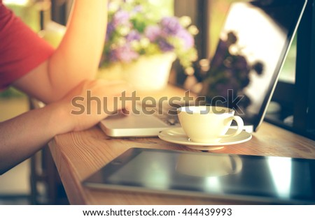 man working on laptop and enjoying coffee in cafe - stock photo