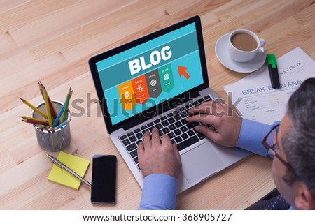 Man working on laptop with BLOG on a screen - stock photo