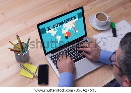 Man working on laptop with E-COMMERCE on a screen - stock photo