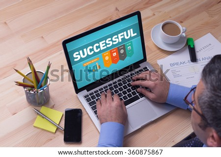 Man working on laptop with SUCCESSFUL on a screen - stock photo