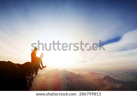 Man working on notebook sitting on cliff on top of the mountains. Concepts of staying online everywhere, internet, freedom reception etc. - stock photo