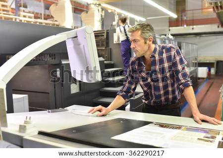 Man working on printing machine in print factory - stock photo