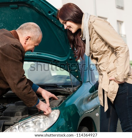 Man working on repairing a woman's car breakdown problem broken - stock photo