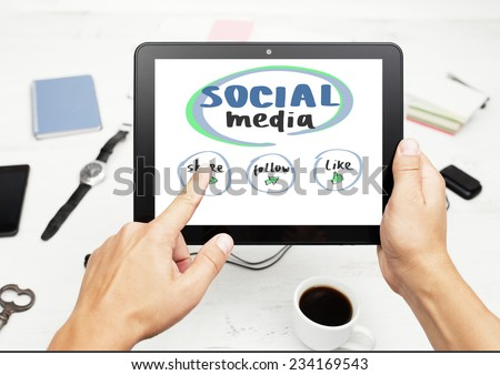 Man working on tablet pc with social media concept on screen, notepad and smart phone on white table. - stock photo