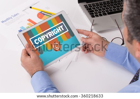 Man working on tablet with COPYRIGHT on a screen - stock photo