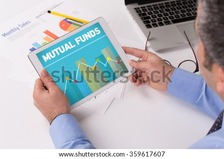 Man working on tablet with MUTUAL FUNDS on a screen - stock photo