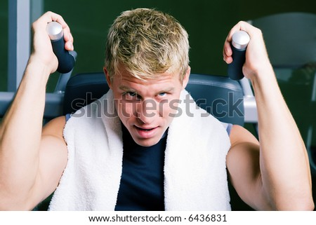 Man working out lifting weights on a machine - stock photo