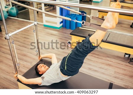 Man working out on a reformer bed  - stock photo