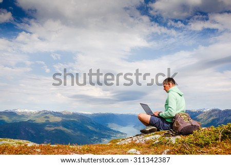 man working outdoors with laptop - stock photo