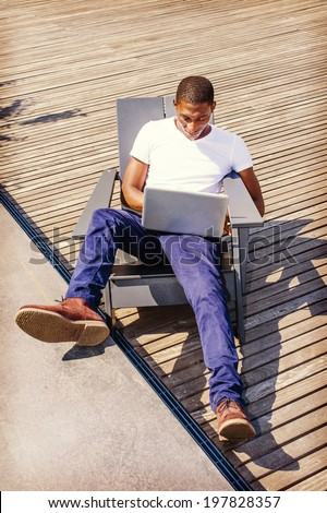 Man Working Outside. Wearing a white V neck T shirt, blue pants, brown boot shoes, a young black guy is casually sitting on a chair on wooden floor, looking down, working on a laptop computer. - stock photo