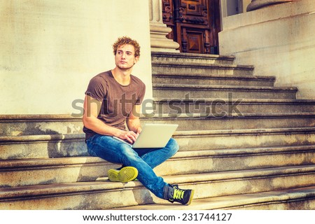 Man Working Outside. Wearing dark brown T shirt, blue jeans, black sneakers, a young sexy guy with curly hair is sitting on stairs outside office, crossing legs, thinking, typing on laptop computer.  - stock photo