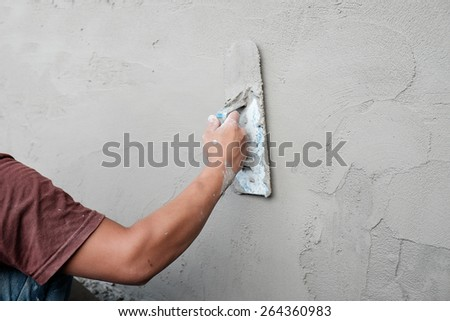 Man working trowel on wet cement wall - stock photo