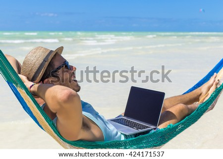 Man working with a laptop, on a hammock in the beach. Concept of digital nomad, remote worker, independent location entrepreneur. - stock photo