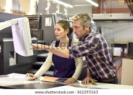 Man working with apprentice in printing house  - stock photo