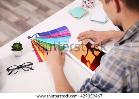 Man working with color palette and tablet at office - stock photo