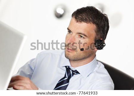 man working with headset and computer in office - stock photo