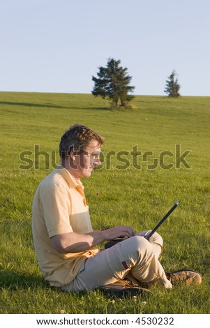 Man working with laptop in a meadow at sunset - stock photo