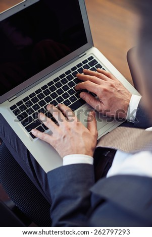 Man working with laptop on knees. - stock photo