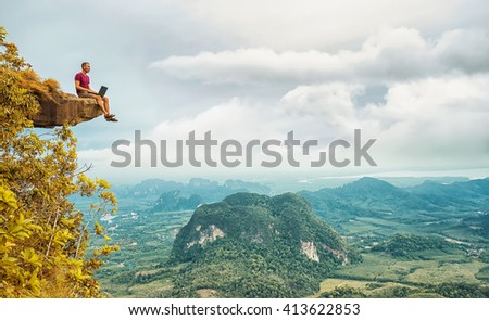 Man working with laptop sitting on the rocky mountain on beautiful scenic clif background. Thailand. Krabi . - stock photo