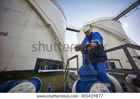 man working with large white fuel containers against blue sky - stock photo