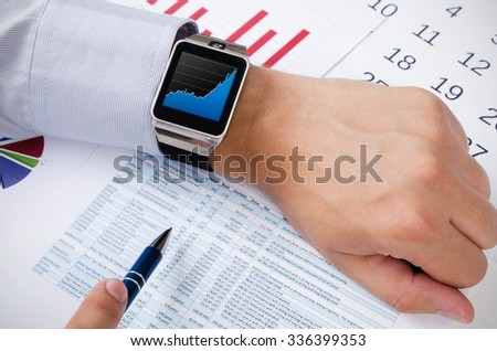Man working with smart watch in office. Chart on screen - stock photo
