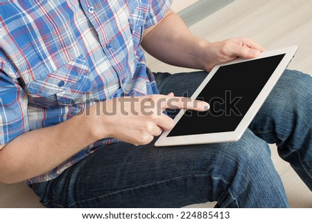 Man works for your tablet while sitting, close-up - stock photo