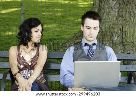 Man works on laptop as woman watches. - stock photo