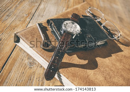 Man wristwatch, calendar, key and glasses on a old table./ Still life on wood background. - stock photo