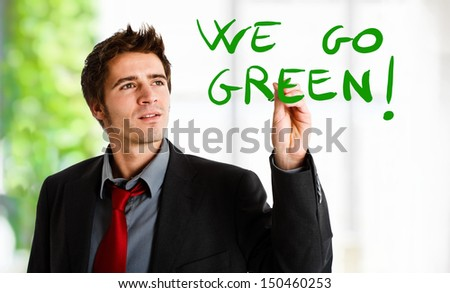 Man writing a green concept on the screen - stock photo