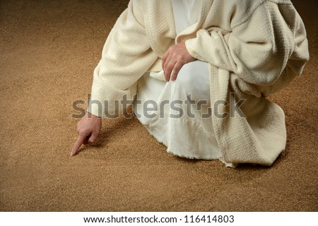 Man writing in the sand with finger - stock photo