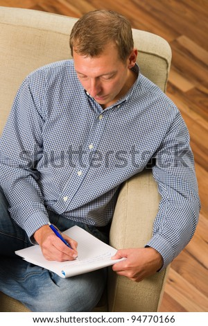 Man writing letter on the armchair. - stock photo