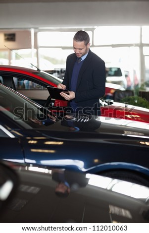 Man writing on a notepad in a garage - stock photo