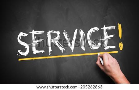 man writing Service! on a blackboard - stock photo