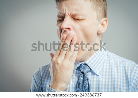 Man yawning and covering his mouth with his hand - stock photo