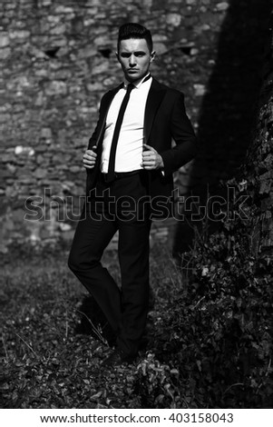 Man young handsome elegant model in unbutton suit coat with skinny necktie poses one leg backward looks in camera outdoor black and white on masonry background - stock photo