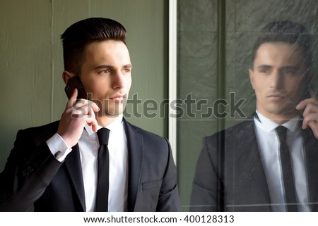 Man young handsome sensual elegant model in suit with skinny necktie open coat talks on mobile phone looks away hand in pocket portrait reflects in mirror on grey background  - stock photo