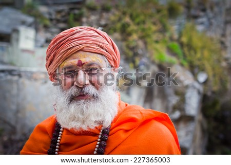 Mana village, India - October 1, 2014: A sadhu man in saffron clothes with smile on face. - stock photo