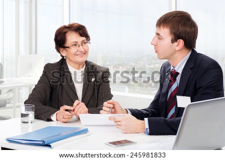 Manager advises the elderly woman in the office - stock photo
