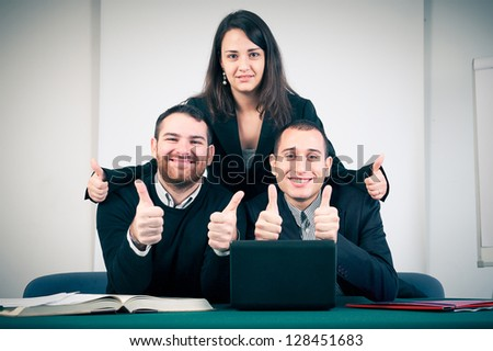 Manager and his team with thumbs up in the office,Italy - stock photo
