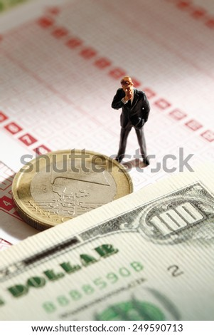Manager figurine standing on betting slip with euro coin and 100 us dollar note - stock photo