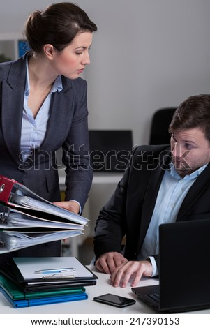 Manager giving assistant a lot of work - stock photo