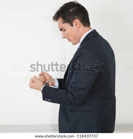 Manager in handcuffs in his office looking sad - stock photo