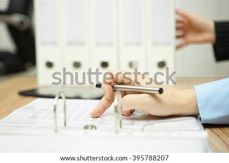Manager is pushing extra paperwork to already very occupied employee - stock photo