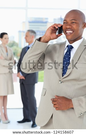 Manager laughing on the phone while his team is in the background - stock photo