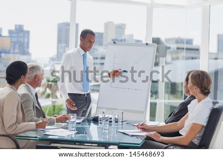 Manager pointing at a growing chart during a meeting in the meeting room - stock photo