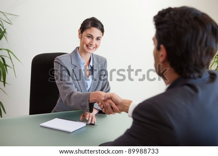 Manager shaking the hand of a customer in her office - stock photo